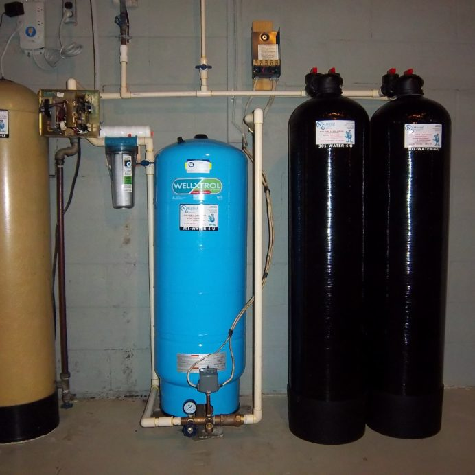 Twin Carbon Tanks for the remediation of cancer causing radon in water added to an existing side mounted Acid Neutralizer for pH & Corrosion control, with a well Water Pressure Tank and a Whole House Sediment Filter