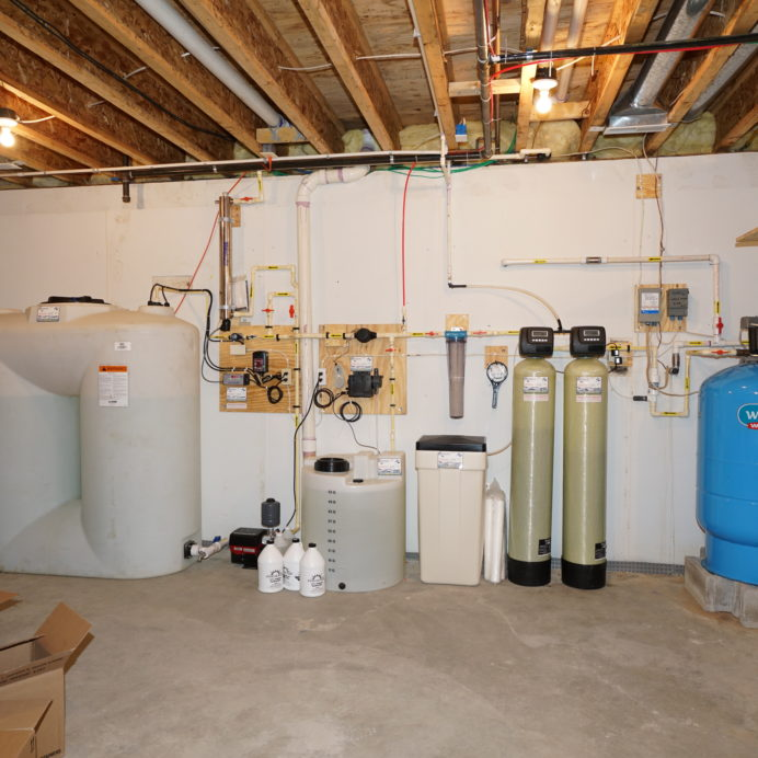 A Water Storage Tank with Pressure Booster Pump, a Chemical Feeder for pH & corrosion control, an Ultra-Violet System to remove all bacteria from water, a Whole House Sediment Filter, a Water Softener with Brine Tank for hard water, a Carbon Tank for odor, smell and remediation of low levels of radon, a Well Water Pressure Tank with Pump Protection Control Center and a Reverse Osmosis System for 99.9% contaminant free cooking & drinking water