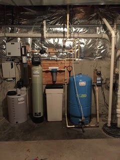 Solution feeder, a water softener, a sediment filter, an ultraviolet disinfection light, a pressure tank and a sump pump