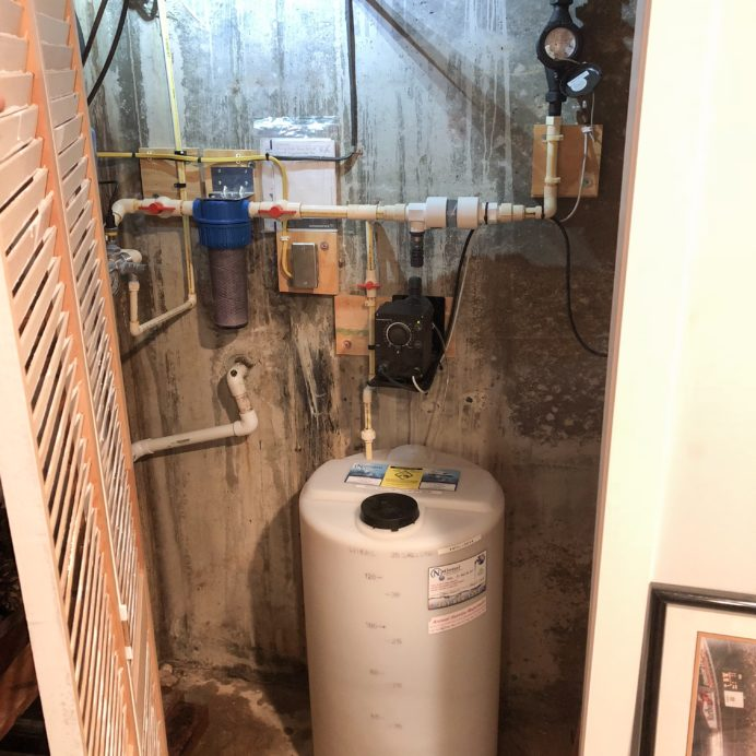 A Chemical Feeder for pH & corrosion control, with a whole house sediment filter in a small water closet